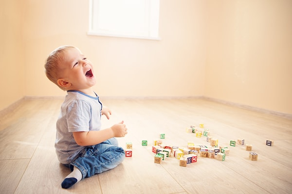 2 year old boy plays with wooden cubes and laughs
